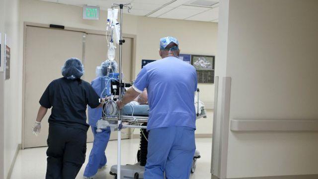 medics wheeling bed through corridor