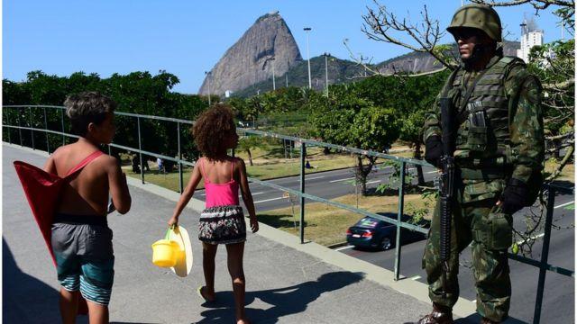 Crianças passam por militar no Rio, às vésperas da cerimônia de abertura da Olimpíada