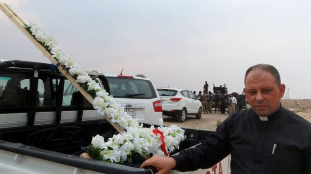 Father Paul Thabet Habib with a flower cross