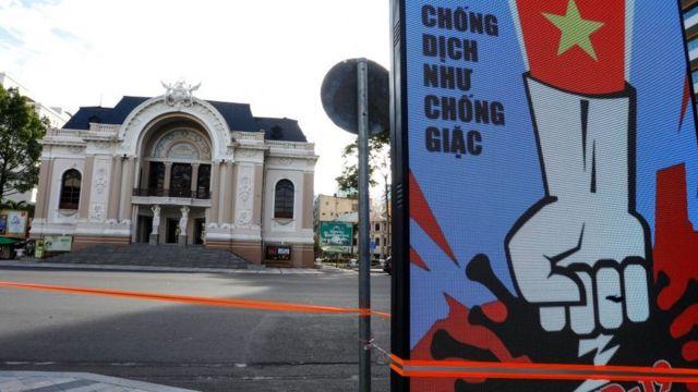 Một khẩu hiệu chống dịch bệnh Covid-19 phía trước Nhà hát lớn ở TP.HCM