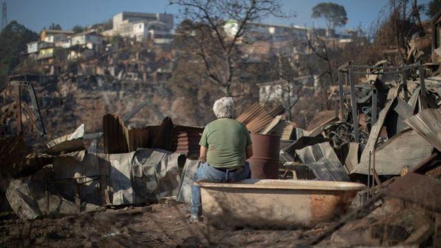 Un hombre sentado en una bañera mira la desolación tras el fuego en Valparaíso.