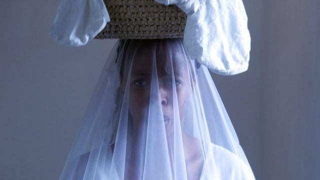 L'artiste Nondumiso Msimanga réalise une performance inspirée par son histoire à elle, en portant une robe de mariée et ceint sa taille avec des culottes blanches déjà portées par d'autres femmes.