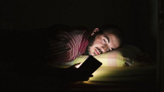 Hombre en la cama, mirando el celular durante la noche