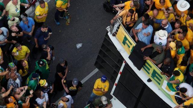 Foto aérea mostra Bolsonaro falando no microfone em cima de trio elétrico, e dezenas de apoiadores em volta e na rua