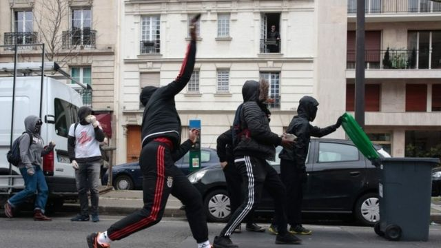 People throw projectiles at riot police during the demonstration against alleged police brutality in Paris (23 February 2017)