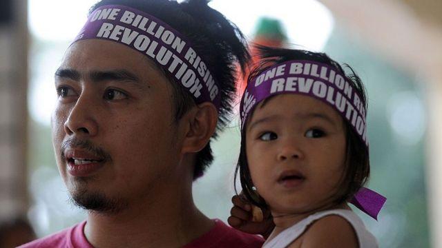 Padre junto su hija durante una campaña defensora de los derechos del niño en Filipinas.