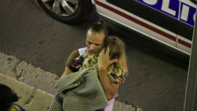 Homem segura criança após caminhão atingir multidão no Dia da Bastilha em Nice (15 Julho 2016)