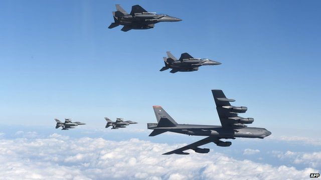 A US B-52 bomber in flight flanked by fighter jets