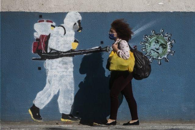 Mulher caminha diante de grafiti no Rio