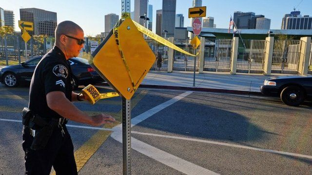 A police officer puts up yellow tape to close a Los Angeles school