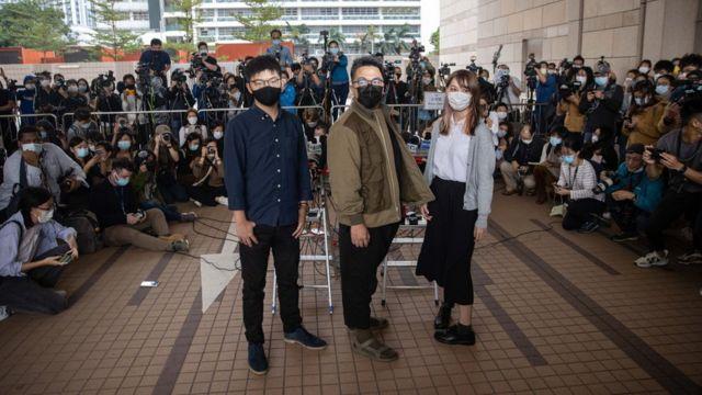 周庭(右)、黄之锋(左)、林朗彦(中)在香港西九龙法院大楼外(23/11/2020)