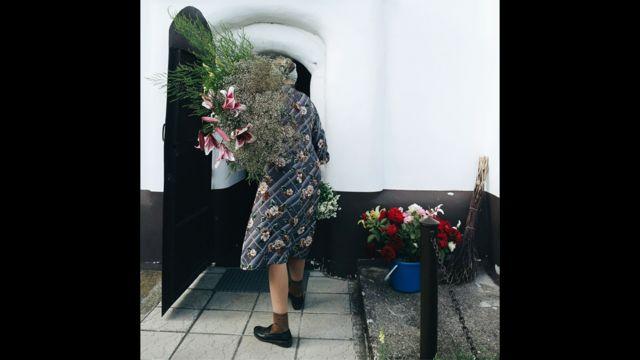 Смотрительница костёла св. Троицы (д. Ишколдь, Республика Беларусь) украшает зал к предстоящей службе