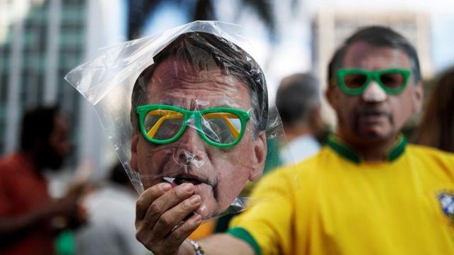 Homem com máscara de Jair Bolsonaro mostra pacote com máscara de Bolsonaro à venda, em manifestação a favor do candidato, em São Paulo