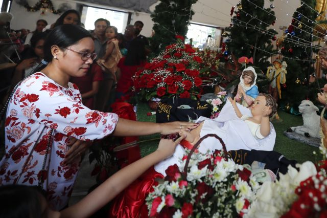 Thai and foreign Catholic church goers touch the baby Jesus doll in the Nativity scene during Christmas Day Mass at a church in Bangkok