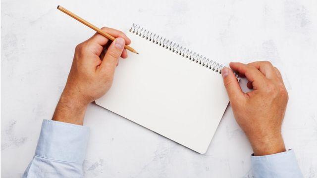 Canhoto escrevendo em caderno