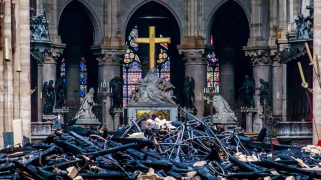 A view of the cross and sculpture of Pieta by Nicolas Coustou in the background of debris inside Notre-Dame de Paris