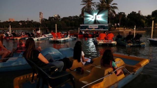 Grupos em embarcações no lago, de tarde, com tela de cinema ao fundo
