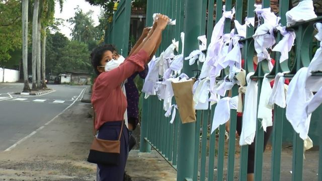 People tying white cloth outside the crematorium