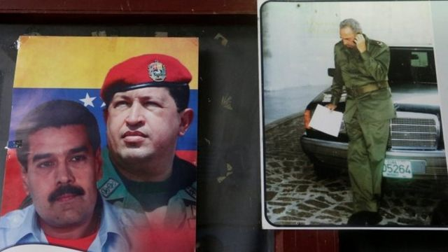 Venezuelan President Nicolas Maduro (left, Venezuela's late President Hugo Chavez (centre) and Cuba's former President Fidel Castro are seen on a wall poster at a state office in Havana (12 July 2017)