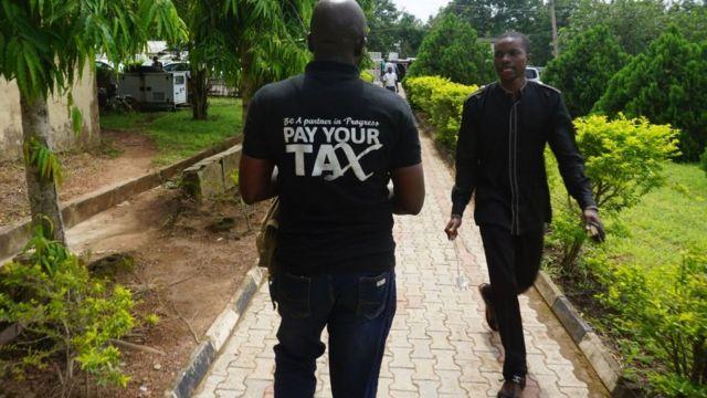 """Man wey wear Tshirt wey dem write """"Pay your tax""""."""