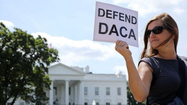 """Una mujer sostiene un papel con el mensaje """"Defiende DACA"""" frente a la Casa Blanca."""