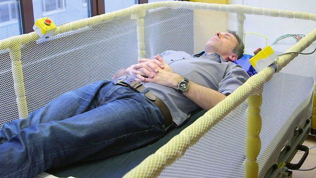 Spencer Kelly lies down in a Somnomat - a bed which rocks you to sleep