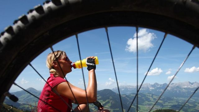 Mulher bebe água após percorrer longo percurso de bicicleta