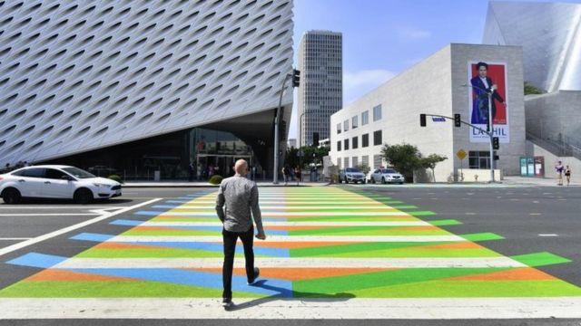 En esta foto tomada el 14 de septiembre de 2017, un hombre cruza un paso peatonal pintado por el artista venezolano Carlos Cruz-Diez frente al al Broad Museum en Los Ángeles, California.