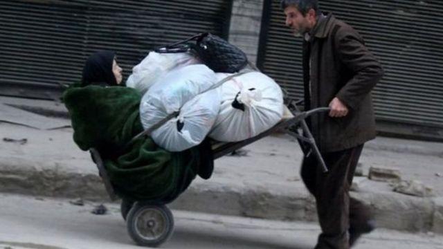 अलेप्पो में एक महिला को ले जाता व्यक्ति