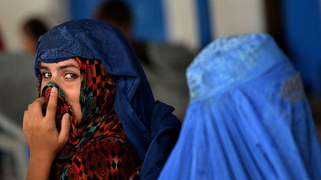 Una joven con el rostro descubierto junto a una mujer con una burka en el centro de repatriación de la ONU en Peshawar