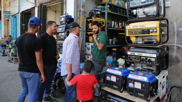 An Iraqi man shops at a store selling power generators in Baghdad