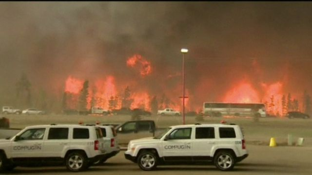 Vehicles driving past towering fires