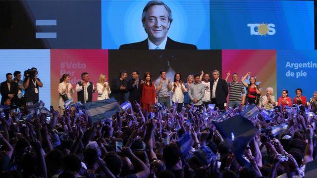 No palco, Alberto Fernandez e a ex-presidente Cristina Kirchner comemoram os resultados das eleições em Buenos Aires, saudados por dezenas de pessoas segurando bandeiras da Argentina no público