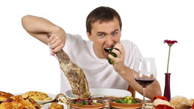 Мужчина за столом с бараньей ногой в руке