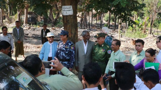 """Former UN secretary-general Kofi Annan (C in grey suit), head of a nine-member multi-sector advisory commission on Myanmar""""s Rakhine State, is accompanied by local military, police officers and government officials in Wapeik, a burned out Rohingya village in Maungdaw located in Rakhine State near Bangladesh border, on December 3, 2016."""