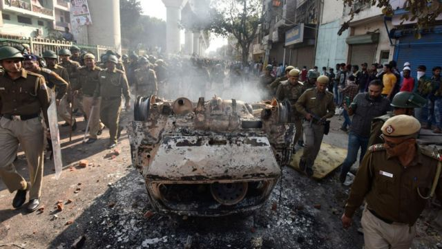 Police walk past a vehicle set on fire by protesters in Delhi