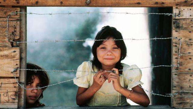 Niña en América Latina detrás de un línea de alambre de púas