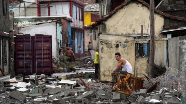 Un hombre sentado sobre los escombros en Baracao
