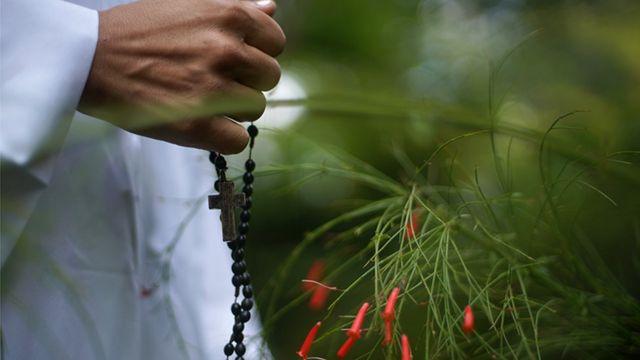 Una mano sosteniendo un rosario