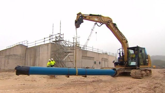 Wessex Water engineers with a crane moving a pipeline