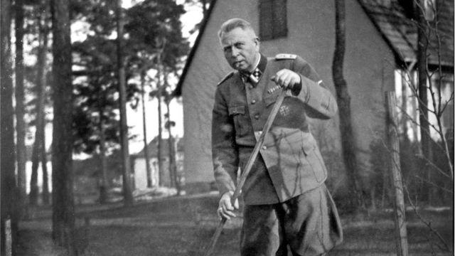 Karl Niemann en su uniforme limpiando el jardín.