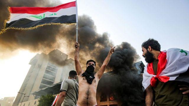 Протестующий, раздетый по пояс и с флагом Ирака