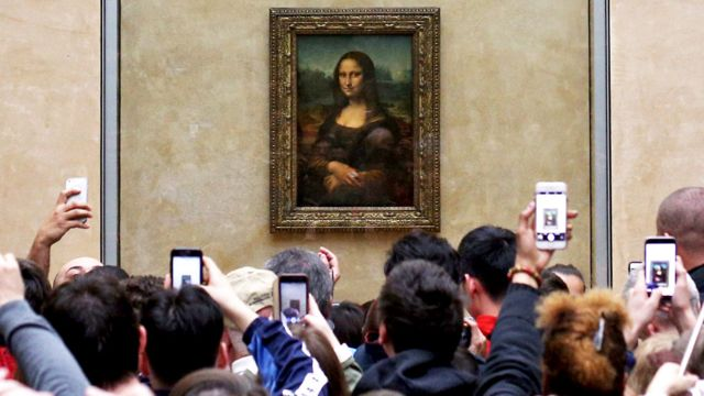 Tourists look at the Mona Lisa painting in the Louvre museum