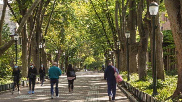 Estudantes universitários caminhando em uma via de pedestres perto da Universidade da Pensilvânia, Filadélfia, EUA