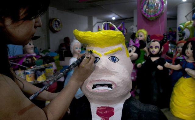 Mujer pinta una piñata de Donald Trump en México.