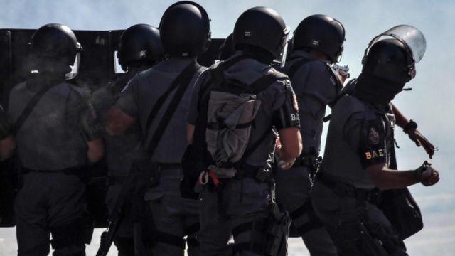 Grupo de policiais de costa, fazendo um paredão, em meio a fumaça e um deles jogando bomba de gás