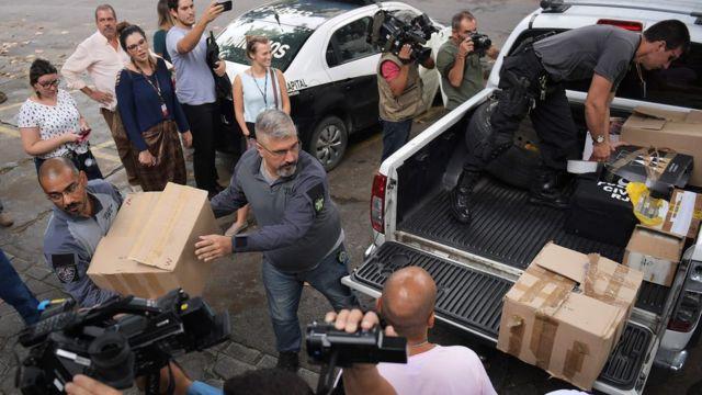 Jornalistas acopmanham retirada de caixas, por policiais civis, com materiais usados nas investigações sobre o caso Marielle