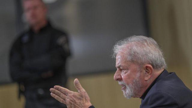 O ex-presidente Lula aparece de perfil falando, com agente de segurança no plano de fundo