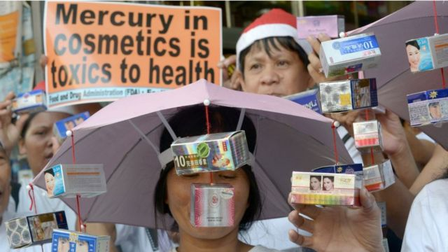 Protestors rally in front of a drug store as they hold cosmetics allegedly tainted with mercury in Manila