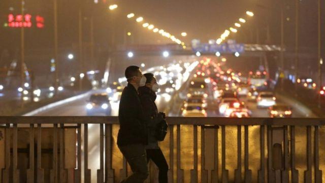夕方のラッシュ時にマスク姿で歩く北京の人たち(7日)